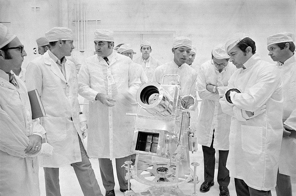 Carruthers discusses the instrument with Apollo 16 Commander John Young, right. From left are Lunar Module Pilot Charles Duke and Rocco Petrone, Apollo Program Director. This photograph was taken during an Apollo lunar surface experiments review in the Manned Spacecraft Operations Building at the Kennedy Space Center. Image #71P-0544 (Circa 1972)